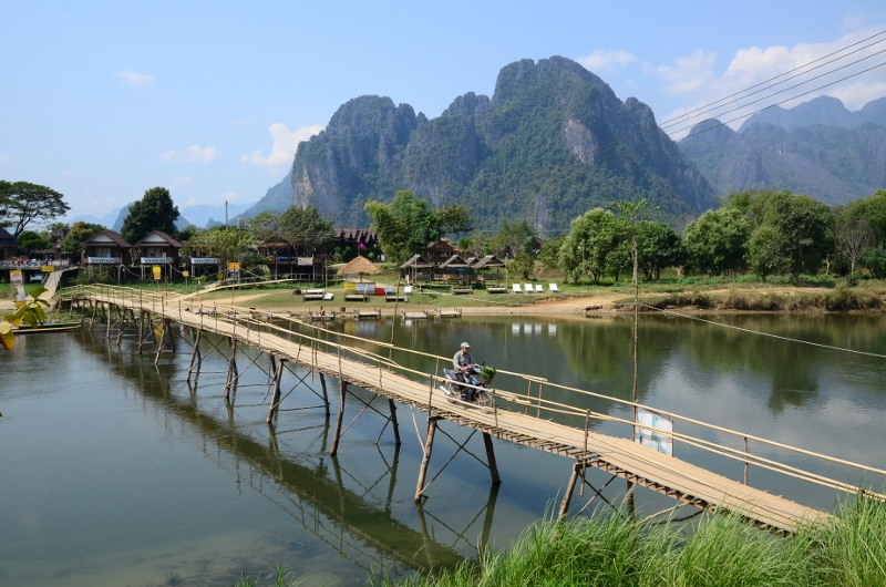 Motorcyklist korsar Nam Song River i Vang Vieng, Laos.