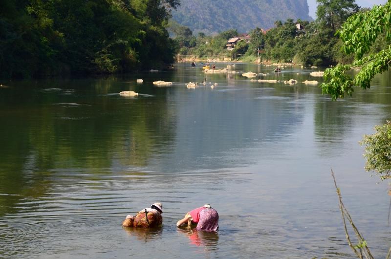 Olya hjälper en lokalbo att fiska för hand i Nam Song River, Vang Vieng.