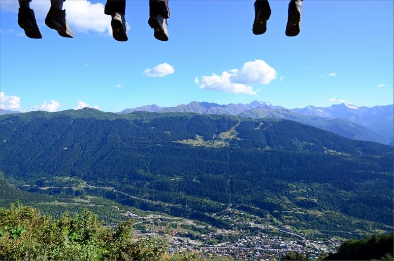 Turister vilar fötterna på plattform vid järnkorset. Mestia nere i dalen och Hatsvali Ski Area på andra sidan.