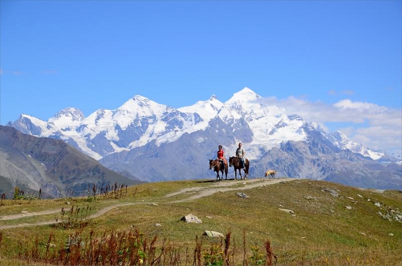 Turister anländer med häst till Koruldi Lakes med Tetnuldi i bakgrunden.