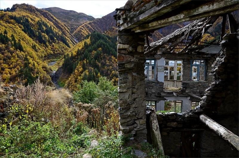 Byggnader i Adishi och ett litet vattenfall i dal på andra sidan dalen.