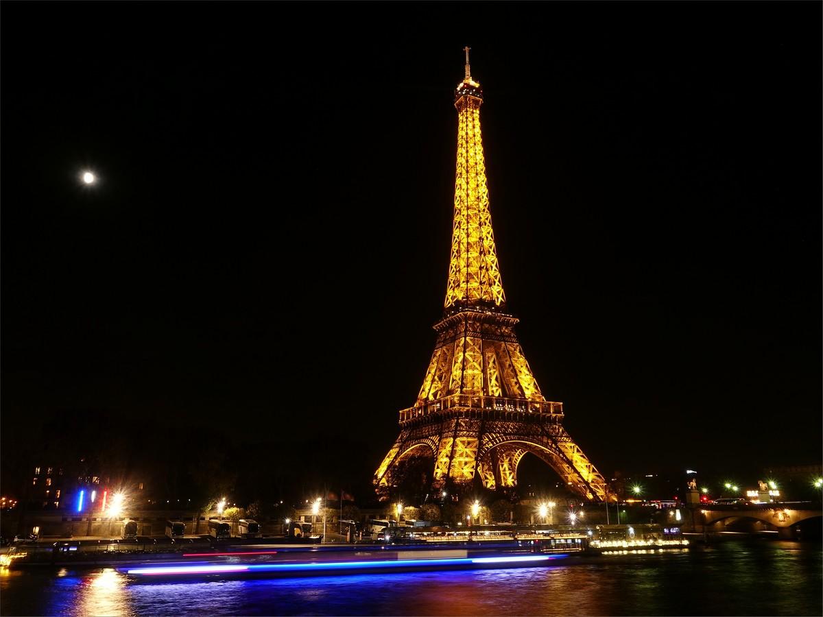 Eiffeltornet och Seinefloden på kvällen. Byggnaden är 300 meter hög och med antenn når den 324 meter.
